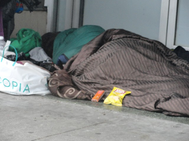 Homeless person sleeping in doorway with potato chips and cheese peanut butter crackers delivered