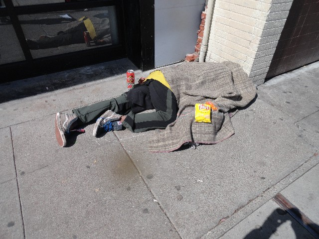 Person laying on sidewalk with potato chips and peanut butter cheese crackers
