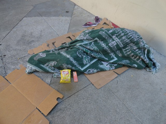 Homeless person sleeping with potato chips and cheese peanut butter crackers delivered
