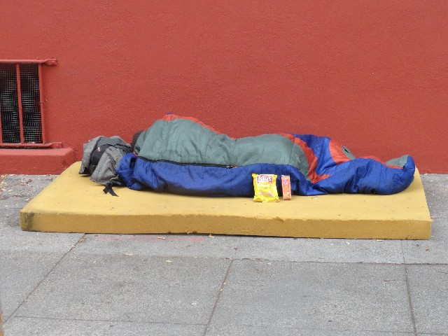 Homeless person sleeps with chips and crackers from the little way homeless outreach charity