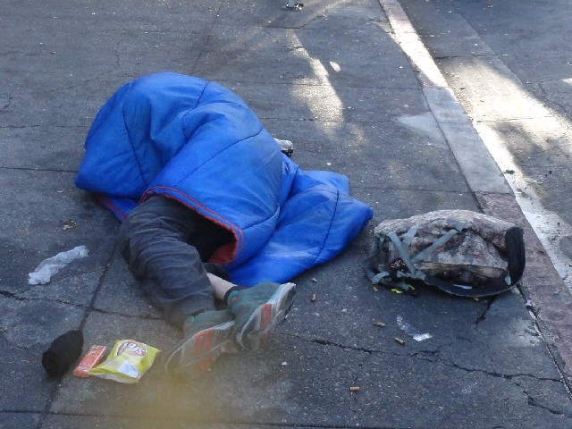 Homeless person lays on sidewalk Berkeley California with food from the little way homeless outreach charity